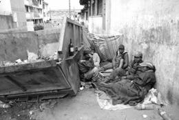 Pauvres habitant derrière un bac à ordures